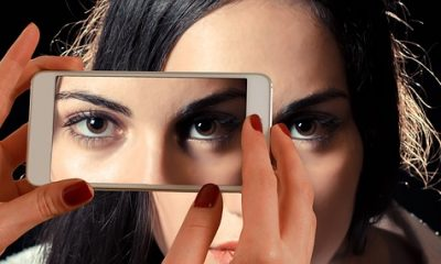 bezel-less smartphone camera capturing a woman's face
